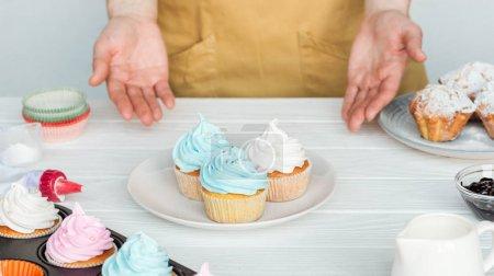 Photo pour Vue recadrée de la femme Gesturant près de l'assiette avec des cupcakes sur la table isolés sur gris - image libre de droit