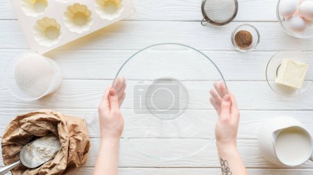 Photo for Cropped view of woman holding glass bowl on table with kitchen utensils and ingredients - Royalty Free Image