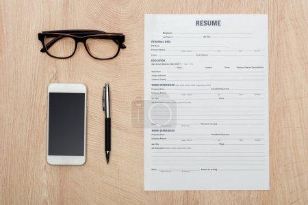 Photo pour Pose plate avec lunettes, stylo, smartphone avec écran vierge et modèle de CV sur la surface en bois - image libre de droit