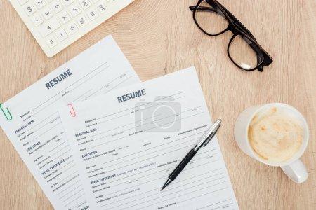 Photo pour Vue du dessus des verres, stylo, calculatrice, tasse de cappuccino et modèles de CV sur la surface en bois - image libre de droit