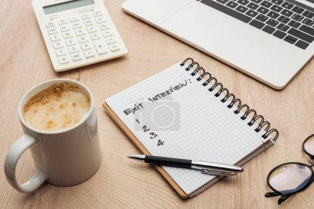 Photo pour Cahier avec le lettrage d'entrevue de sortie et les nombres sur la table en bois avec l'ordinateur portatif, la papeterie, les glaces et la tasse de café - image libre de droit
