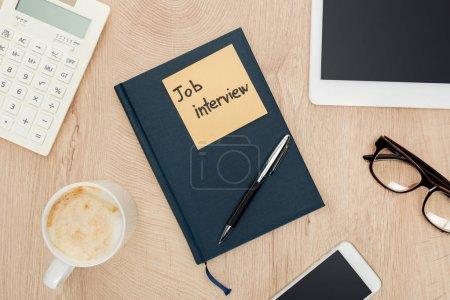 Photo pour Vue supérieure du stylo sur le cahier avec le lettrage de vue d'emploi sur la note collante sur la table en bois avec des gadgets et une tasse de café - image libre de droit
