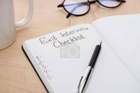 notebook with exit interview checklist lettering and numbers on wooden table with pen, glasses and cup