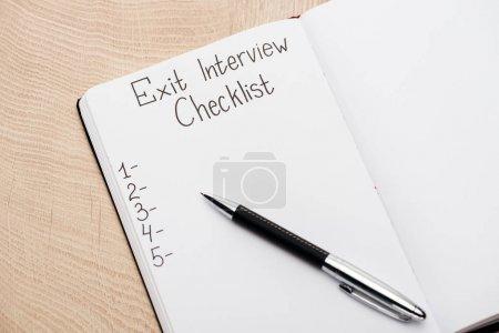 Photo pour Cahier avec stylo, lettrage de liste de contrôle d'entrevue de sortie et nombres sur la table en bois - image libre de droit