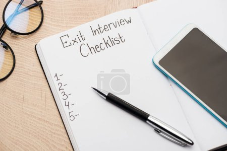 notebook with exit interview checklist lettering and numbers on wooden table near smartphone, pen and glasses
