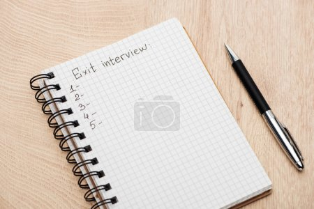 notebook with pen, exit interview lettering and numbers on wooden table