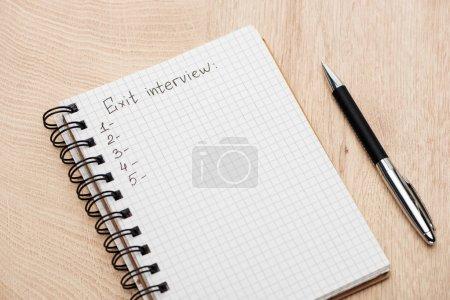 Photo pour Cahier avec le stylo, lettrage d'entrevue de sortie et nombres sur la table en bois - image libre de droit