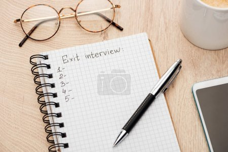 notebook with exit interview lettering, copy space and numbers on wooden table near smartphone, pen, glasses and coffee cup