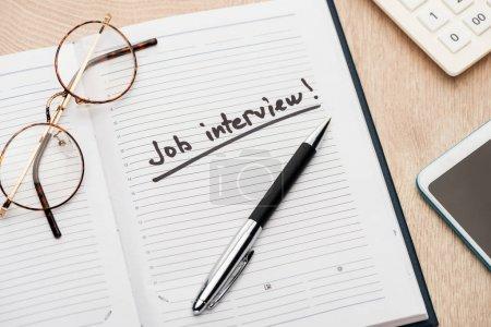 Photo pour Cahier avec le stylo, les glaces et le lettrage d'entrevue d'emploi sur la table en bois - image libre de droit