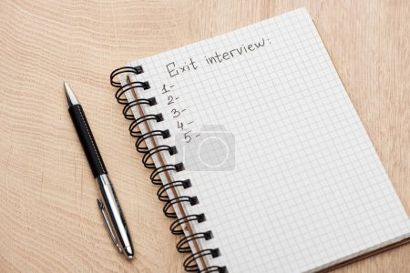 Photo for Notebook with exit interview lettering, copy space and numbers on wooden table near pen - Royalty Free Image
