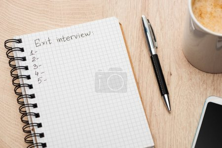 notebook with exit interview lettering, copy space and numbers on wooden table near smartphone, pen and coffee cup