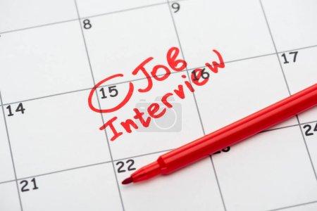 Photo pour Fermer le calendrier d'impression avec la marque rouge et le lettrage d'entrevue d'emploi - image libre de droit