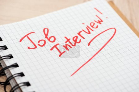 Photo pour Cahier avec le lettrage rouge d'entrevue d'emploi sur la table en bois - image libre de droit
