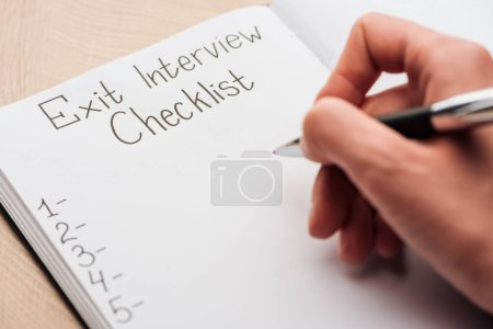 Photo for Cropped view of recruiter writing in notebook with exit interview checklist lettering - Royalty Free Image
