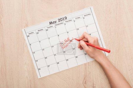 Photo pour Vue recadrée de l'écriture de recruteur avec le marqueur rouge sur le calendrier d'impression avec le lettrage d'entrevue d'entrevue d'emploi - image libre de droit