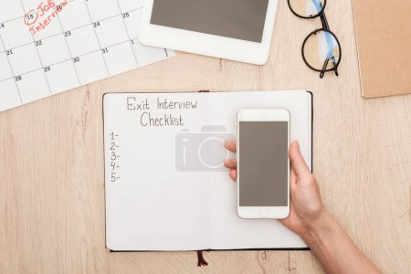Photo for Cropped view of recruiter holding smartphone with blank screen above notebook with exit interview checklist lettering - Royalty Free Image