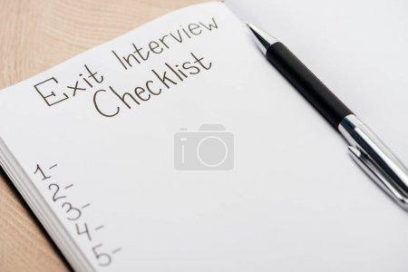 Photo pour Fermer le cahier avec le lettrage et le stylo de liste de contrôle d'entrevue de sortie - image libre de droit
