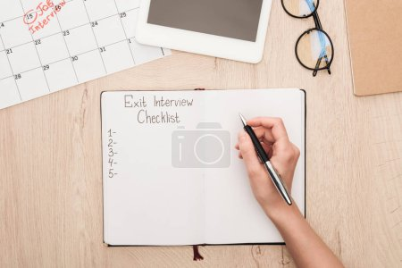 Photo for Partial view of recruiter holding pen near notebook with exit interview checklist lettering - Royalty Free Image