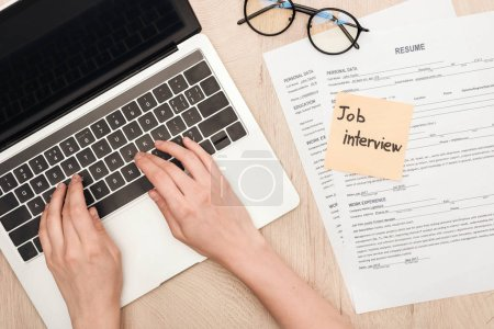 Photo for Cropped view of recruiter typing on laptop keyboard near glasses, resume templates and sticky note with job interview lettering - Royalty Free Image