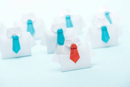 Foto de Selective focus of origami white shirts with blue ties with one red on blue background, leadership concept - Imagen libre de derechos