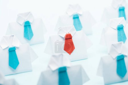 Foto de Selective focus of origami white shirts with blue ties with one red on blue background, think different concept - Imagen libre de derechos