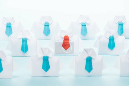 Foto de Origami white shirts with blue ties with one red on blue background, think different concept - Imagen libre de derechos
