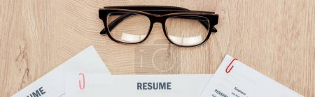 Photo for Panoramic shot of resume templates and glasses on wooden table - Royalty Free Image