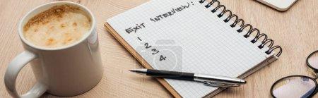 Photo pour Tir panoramique de cahier avec le lettrage d'entrevue de sortie et les nombres sur la table en bois avec le stylo, les glaces et la tasse de café - image libre de droit