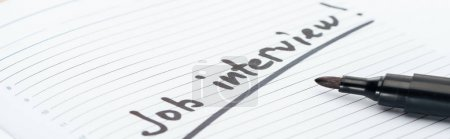 Photo for Panoramic shot of job interview lettering on white paper near black marker - Royalty Free Image