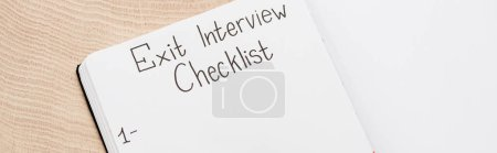 Photo for Panoramic shot of notebook with exit interview checklist lettering and number on wooden table - Royalty Free Image