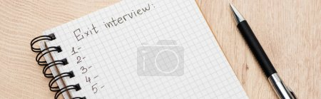 Photo for Panoramic shot of notebook with exit interview lettering and numbers on wooden surface with pen - Royalty Free Image