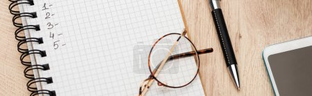 Photo for Panoramic shot of notebook with numbers on wooden surface with pen, glasses and smartphone - Royalty Free Image
