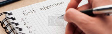 panoramic shot of recruiter writing in notebook with exit interview lettering