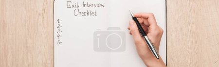 panoramic shot of recruiter writing in notebook with exit interview checklist lettering