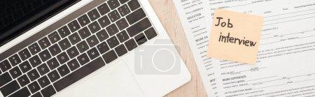 Panoramaaufnahme von Laptop, Lebenslauf-Vorlagen und Haftnotiz mit Jobinterview-Schriftzug auf Holztisch