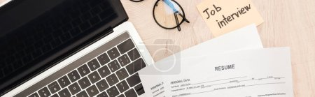 Photo for Panoramic shot of laptop, glasses, resume templates and sticky note with job interview lettering on wooden table - Royalty Free Image