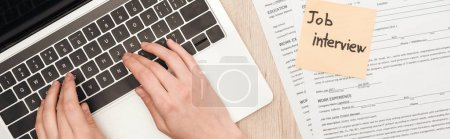 Photo for Panoramic shot of recruiter typing on laptop keyboard near resume templates and sticky note with job interview lettering - Royalty Free Image