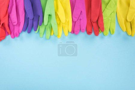 Foto de Guantes de goma multicolores sobre fondo azul con espacio de copia - Imagen libre de derechos
