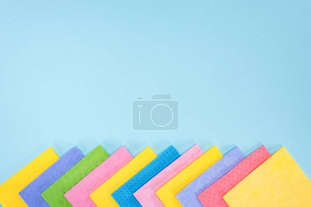 Photo pour Multicolored rags on blue background with copy space - image libre de droit