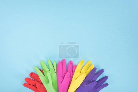 Photo pour Vue supérieure des gants en caoutchouc multicolores sur le fond bleu avec l'espace de copie - image libre de droit