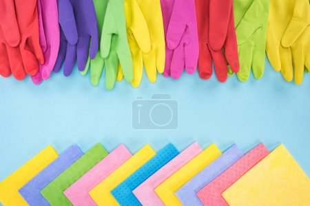 Photo for Top view of multicolored bright rubber gloves and rags on blue background with copy space - Royalty Free Image