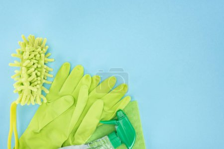 Photo for Top view of green rubber gloves, sponge, rag and spray bottle with detergent on blue background with copy space - Royalty Free Image