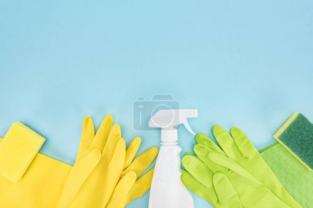 Photo for Top view of yellow and green rubber gloves, sponges, rags and spray bottle with detergent on blue background with copy space - Royalty Free Image