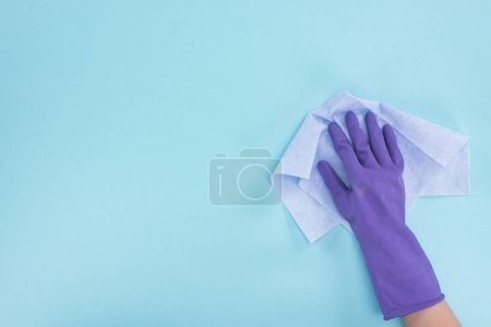 Photo for Cropped view of cleaner in purple rubber glove holding rag on blue background - Royalty Free Image