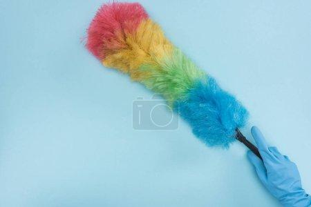 Foto de Vista recortada del limpiador en guante de goma sosteniendo el polvodel arco iris sobre fondo azul - Imagen libre de derechos