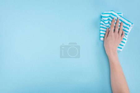 Photo for Cropped view of woman holding striped rag on blue background - Royalty Free Image