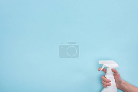 Photo for Cropped view of woman holding white spray bottle with detergent on blue background - Royalty Free Image