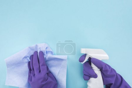 Photo for Cropped view of cleaner in purple rubber gloves holding rag and spray bottle with detergent on blue background - Royalty Free Image