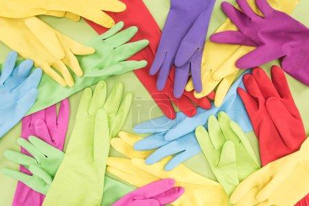 Foto de Vista superior de los guantes de goma multicolordispersos desordenados sobre fondo verde - Imagen libre de derechos