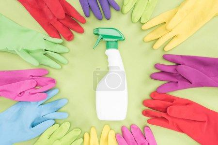 Photo pour Vue supérieure des gants en caoutchouc multicolores en cercle autour de la bouteille de pulvérisation avec le détergent sur le fond vert - image libre de droit